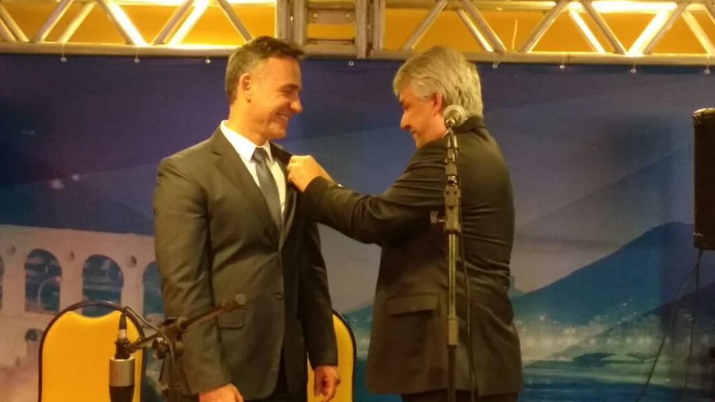 Dr. Caetano Marchesini, eleito próximo presidente da SBCBM, recebe o pin do Dr. Josemberg Campos, atual presidente.